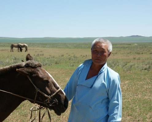 Mongolian cashmere grower with horse